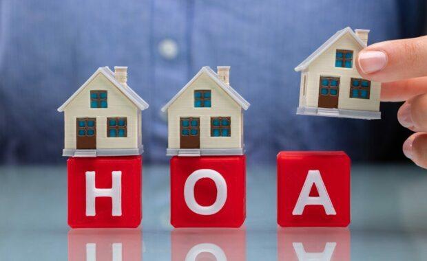 女商人将房子模型放在桌子上的红色方块上