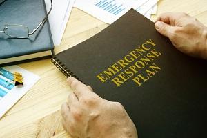 商业物业管理人员打开灾难和紧急应变计划阅读